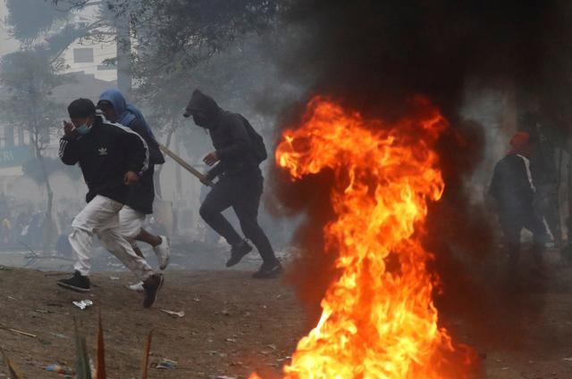 FILE PHOTO: Demonstrators run past a fire during a protest against Ecuador's President Lenin Moreno's austerity measures, in Quito, Ecuador October 13, 2019.  REUTERS/Henry Romero