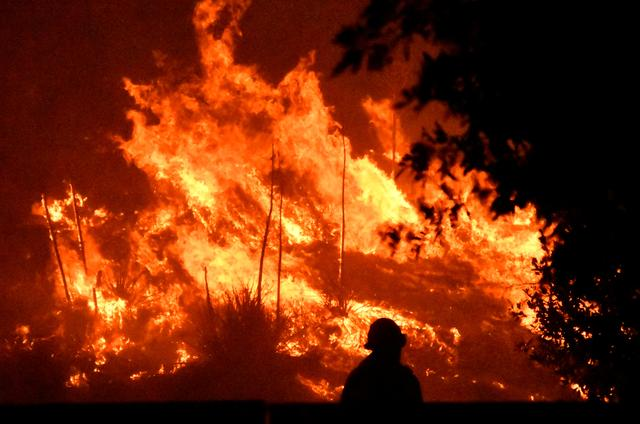 FILE PHOTO: Firefighters battle a wind-driven wildfire called the Saddle Ridge fire in the early morning hours Friday in Porter Ranch, California, U.S., October 11, 2019.  REUTERS/Gene Blevins