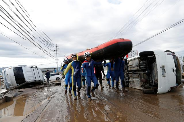 Rescue workers carry a rubber dinghy as they search a flooded area in the aftermath of Typhoon Hagibis, which caused severe floods at the Chikuma River in Nagano Prefecture, Japan, October 14, 2019. REUTERS/Kim Kyung-Hoon