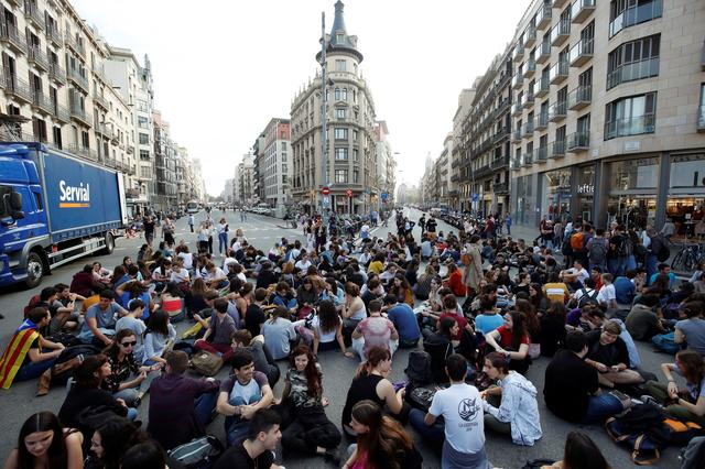 Students sit at Plaza Universidad after a verdict in a trial over a banned independence referendum, in Barcelona, Spain October 14, 2019. REUTERS/Albert Gea