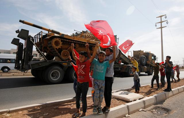 Boys wave Turkish flags as a military convoy drives near the border town of Akcakale in Sanliurfa province, Turkey, October 14, 2019. REUTERS/Kemal Aslan