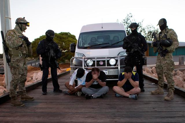 Police officers stand around suspects arrested during an operation that, according to police, resulted in the seizure of 1.2 tonnes of methamphetamine in Geraldton, Australia, December 21, 2017. Picture taken December 21, 2017.   Australian Federal Police/Handout via REUTERS