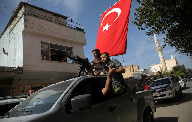 Turkish-backed Syrian rebels drive on a street in the Turkish border town of Akcakale in Sanliurfa province, Turkey, October 14, 2019. REUTERS/Stoyan Nenov