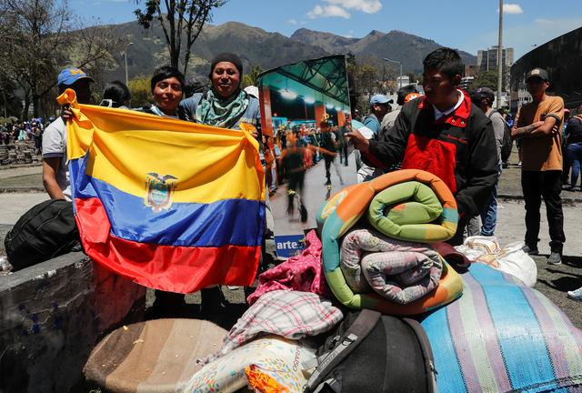 People hold an Ecuadorian flag as they participate in a cleanup of the streets in the aftermath of the last days' protests, after the government of Ecuadorian President Lenin Moreno agreed to repeal a decree that ended fuel subsidies, in Quito, Ecuador October 14, 2019. REUTERS/Henry Romero