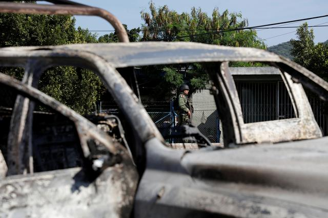 A soldier is seen near the burnt wreckage of a police patrol car after an ambush by suspected cartel on police officers in El Aguaje, in Michoacan state, Mexico October 14, 2019. REUTERS/Alan Ortega