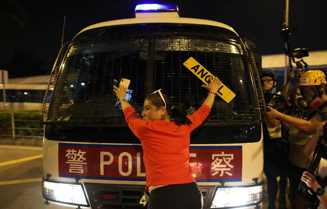 FILE PHOTO: An anti-government demonstrator stands in fron of a police vehicle during a protest against the invocation of the emergency laws in Hong Kong, China, October 14, 2019. REUTERS/Ammar Awad/File Photo