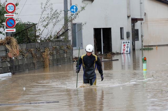 A rescue worker wades in water in the aftermath of Typhoon Hagibis, which caused severe floods, near the Chikuma River in Nagano Prefecture, Japan, October 14, 2019. REUTERS/Kim Kyung-Hoon
