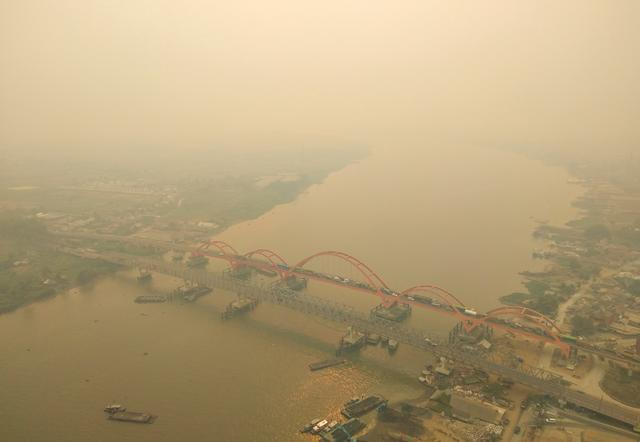 An aerial view of Palembang city covered by smoke from the forest fire in South Sumatra province, Indonesia, October 14, 2019 in this photo taken by Antara Foto.  Antara Foto/Nathan/ via REUTERS