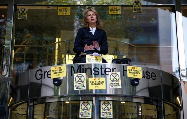 Co-founder of the Extinction Rebellion group, Gail Bradbrook, sits atop the doorway into the Department of Transport, during an Extinction Rebellion protest in London, Britain, October 15, 2019. REUTERS/Henry Nicholls