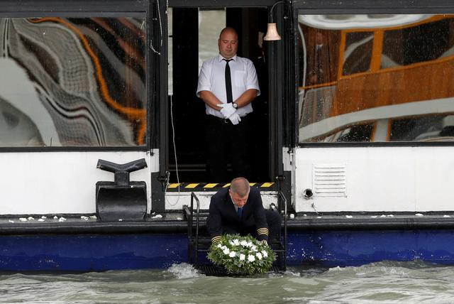 FILE PHOTO: A man lays a wreath near the Margeret bridge during a special funeral ceremony of the Hungarian captain and crew of the boat Mermaid, that had sunk in the Danube with a group of South Korean tourists on board, in May, Budapest, Hungary July 12, 2019. REUTERS/Bernadett Szabo/File Photo