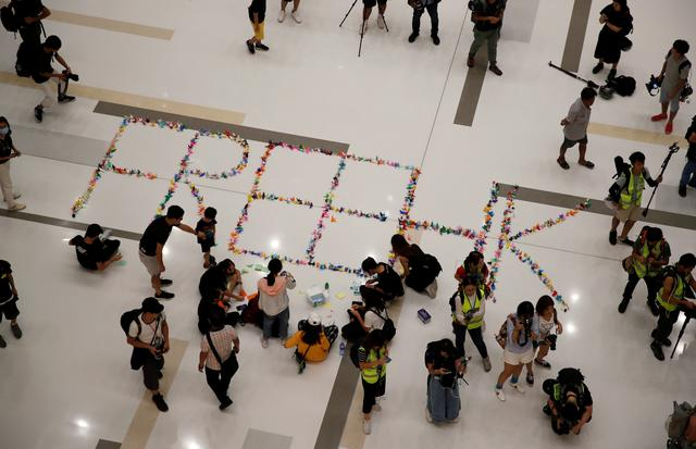 """Anti-government protesters form a sign reading """"Free HK"""" from folded paper birds during a demonstration at New Town Plaza shopping mall in Hong Kong, China, October 12, 2019. REUTERS/Umit Bektas"""