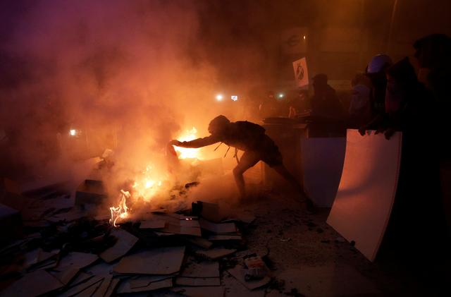 A separatist demonstrator puts an object into a fire during a protest after a verdict in a trial over a banned independence referendum in Barcelona, Spain, October 15, 2019. REUTERS/Albert Gea