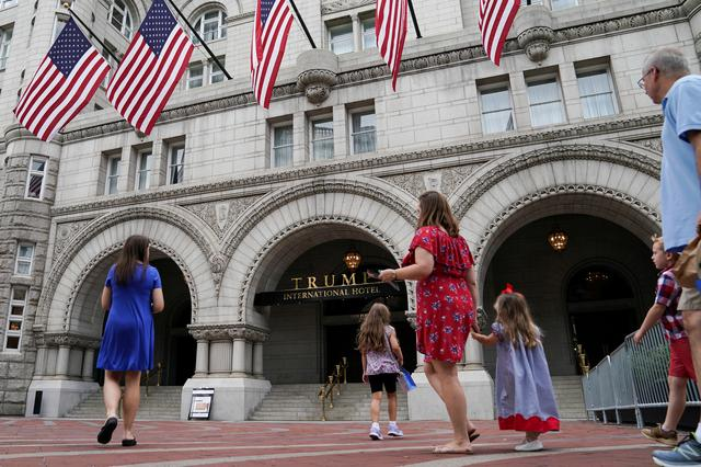 FILE PHOTO: A group of people approach the front facade of the Trump International Hotel to pose for photos in Washington, U.S., July 31, 2019. REUTERS/Sarah Silbiger/File Photo