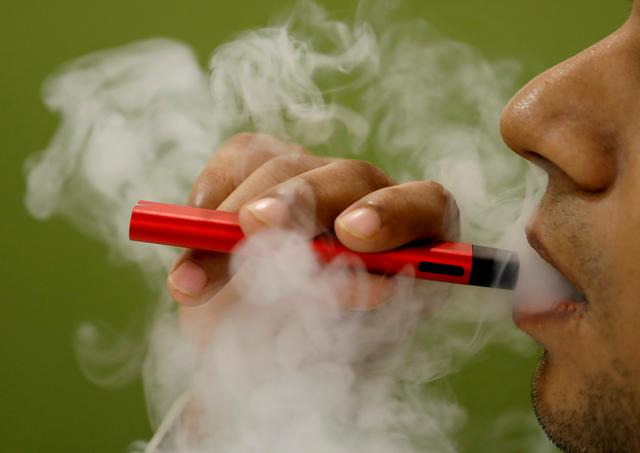 FILE PHOTO: A man uses a vape device in this illustration picture, September 19, 2019. REUTERS/Adnan Abidi/Illustration/File Photo