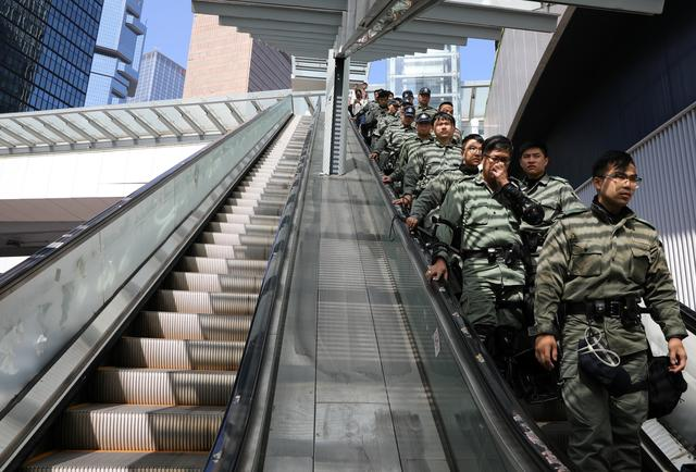 Police officers stand guard on an escalator ahead of Hong Kong Chief Executive Carrie Lam's annual policy address, after four months of anti-government protests, at the Legislative Council in Hong Kong, China, October  16, 2019. REUTERS/Ammar Awad