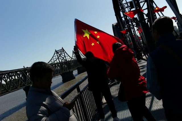 A Chinese visitor poses for picture with a Chinese flag on the Broken Bridge near the Friendship Bridge which connects North Korea's Sinuiju and China over the Yalu river, in Dandong, Liaoning province, China October 5, 2019. Picture taken October 5, 2019. REUTERS/Thomas Suen
