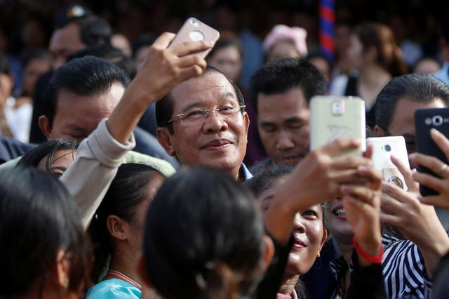 FILE PHOTO: Garment workers welcome Cambodia's Prime Minister Hun Sen during a rally in Kandal province, Cambodia May 30, 2018. To match Special Report CAMBODIA-HUNSEN/WEALTH      REUTERS/Stringer/File Photo
