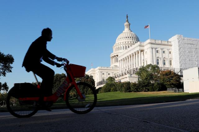 A man rides his bike past the U.S. Capitol Building in Washington, U.S., October 15, 2019. REUTERS/Carlos Jasso