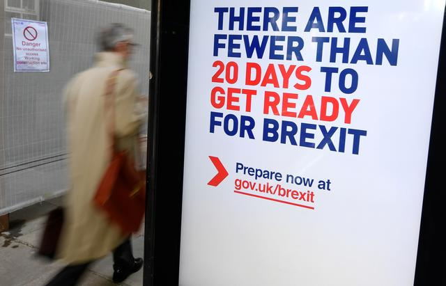 A man walks past an UK government Brexit information campaign poster at a bus stop in central London, Britain, October 15, 2019. REUTERS/Toby Melville