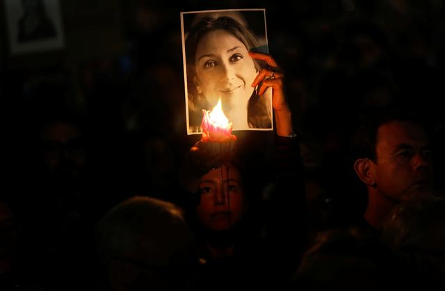 A person hold a candle in front of a picture of anti-corruption journalist Daphne Caruana Galizia, during a vigil and protest on the second anniversary of assassination of the journalist in a car bomb, in Valletta, Malta October 16, 2019. REUTERS/Darrin Zammit Lupi