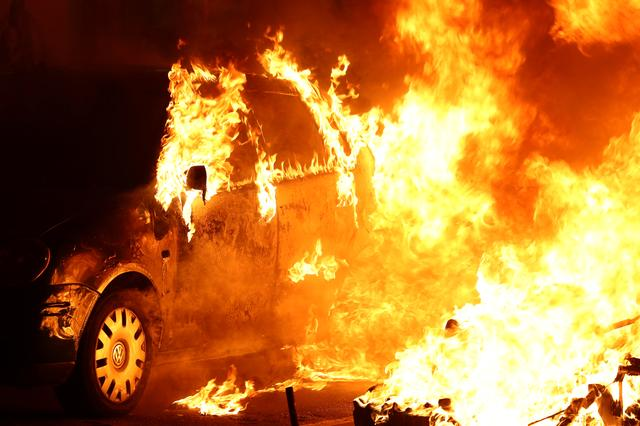 A car burns during a protest after a verdict in a trial over a banned Catalonia's independence referendum in Barcelona, Spain, October 16, 2019. REUTERS/Jon Nazca