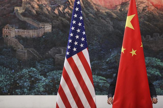 FILE PHOTO: A Chinese man adjusts a China flag before a news conference attended by Chinese Foreign Minister Yang Jiechi and U.S. Secretary of State Hillary Clinton at the Great Hall of the People in Beijing September 5, 2012.  REUTERS/Feng Li/Pool