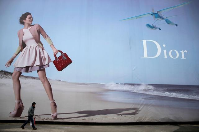 FILE PHOTO: A man walks past a Dior advertisement outside a shopping mall in Wuhan, Hubei province, January 19, 2013. REUTERS/Stringer/File Photo