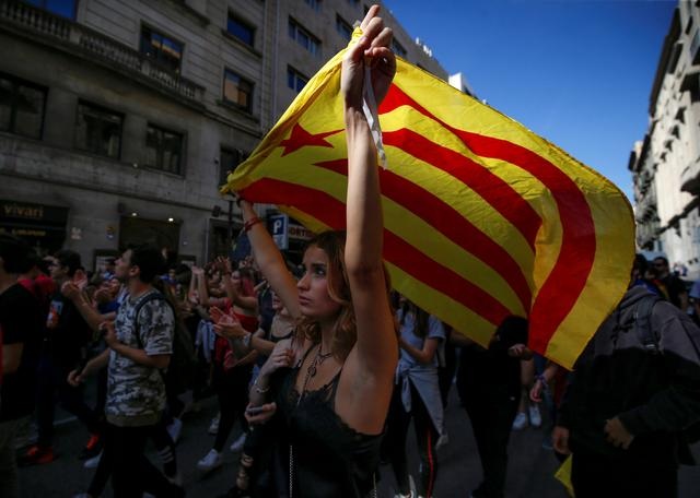 A woman waves an Estelada (Catalan separatist flag) during a protest after Spain's Supreme Court jailed nine separatist leaders, triggering violent protests in the region, in Barcelona, Spain, October 17, 2019. REUTERS/Rafael Marchante
