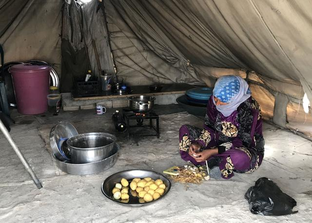A woman prepares food in the Mabrouka camp, near Ras al-Ain, Syria October 16, 2019. PREUTERS/Aboud Hamam