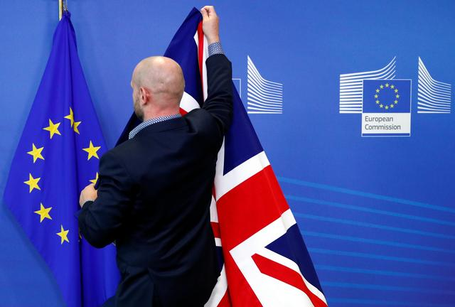 A staff member hangs a Union Jack next to an EU flag ahead of a meeting of European Commission President Jean-Claude Juncker and Britain's Prime Minister Boris Johnson at the sidelines of the European Union leaders summit, in Brussels, Belgium October 17, 2019. REUTERS/Francois Lenoir
