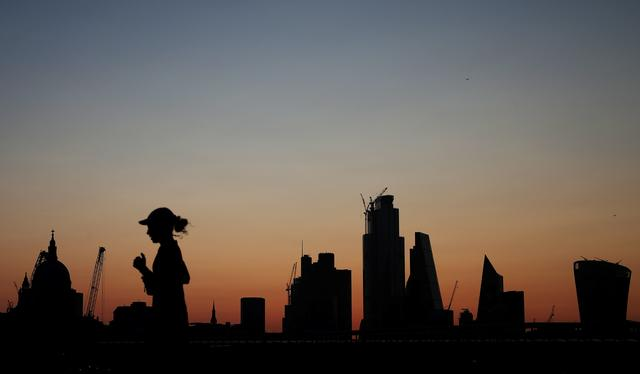 FILE PHOTO: A woman jogs as the sun rises behind the city of London financial district in London, Britain August 20, 2019. REUTERS/Hannah McKay/File Photo