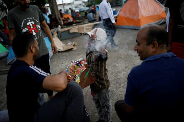 FILE PHOTO: A boy selling candies and cigarettes gestures to the camera as he argues with migrants from India outside of Siglo XXI migration facility in Tapachula, Mexico, May 13, 2019. REUTERS/Andres Martinez Casares/File Photo