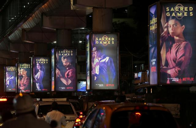 """FILE PHOTO: Traffic moves on a road past hoardings of Netflix's new television series """"Sacred Games"""" in Mumbai, India, July 11, 2018. REUTERS/Francis Mascarenhas/File Photo"""