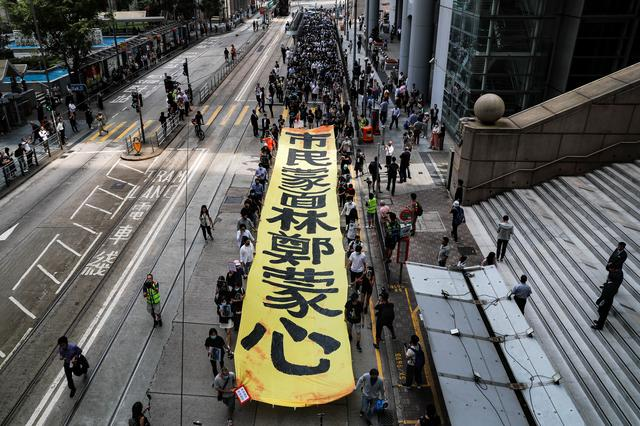 People march with a banner to protest against what they say is the abuse of pro-democracy protesters by Hong Kong police, near Chater Garden in Central district, Hong Kong, China October 18, 2019. REUTERS/Ammar Awad