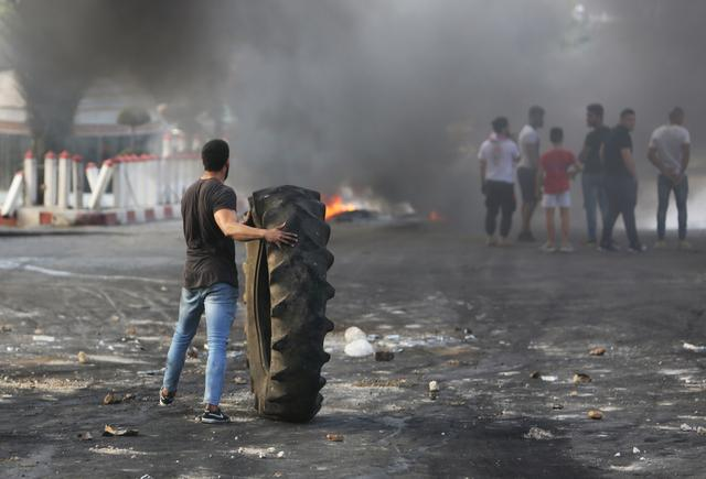 A demonstrator holds a tire during a protest targeting the government over an economic crisis, in Nabatiyeh, southern Lebanon October 18, 2019. REUTERS/Aziz Taher