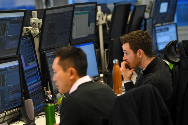 FILE PHOTO: Dealers work at their desks whilst screens show market data following a vote on Prime Minister Theresa May's Brexit 'plan B' at CMC Markets in London, Britain, January 30, 2019. REUTERS/Dylan Martinez