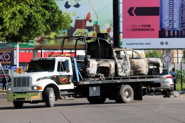 """A tow truck transports the burnt wreckage of a police patrol truck a day after cartel gunmen clashed with federal forces, resulting in the release of Ovidio Guzman from detention, the son of drug kingpin Joaquin """"El Chapo"""" Guzman, in Culiacan, in Sinaloa state, Mexico October 18, 2019. REUTERS/Stringer"""
