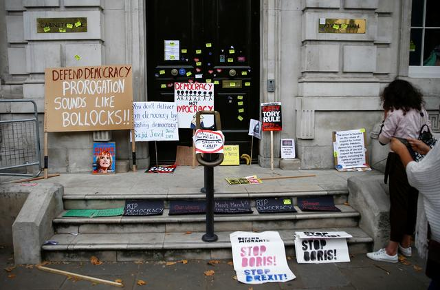 FILE PHOTO: Stickers and placards are seen attached to the CabinetOffice door during a anti-Brexit protest, at Westminster in London, Britain, August 31, 2019. REUTERS/Henry Nicholls