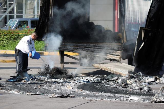"FILE PHOTO: A police officer pours water on the burnt wreckage of a truck a day after cartel gunmen clashed with federal forces, resulting in the release of Ovidio Guzman from detention, the son of drug kingpin Joaquin ""El Chapo"" Guzman, in Culiacan, in Sinaloa state, Mexico October 18, 2019. REUTERS/Stringer"