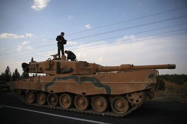 FILE PHOTO: Turkish soldiers stand atop of a tank as army vehicles are moving on a road near the Turkish border town of Ceylanpinar, Sanliurfa province, Turkey, October 18, 2019. REUTERS/Stoyan Nenov
