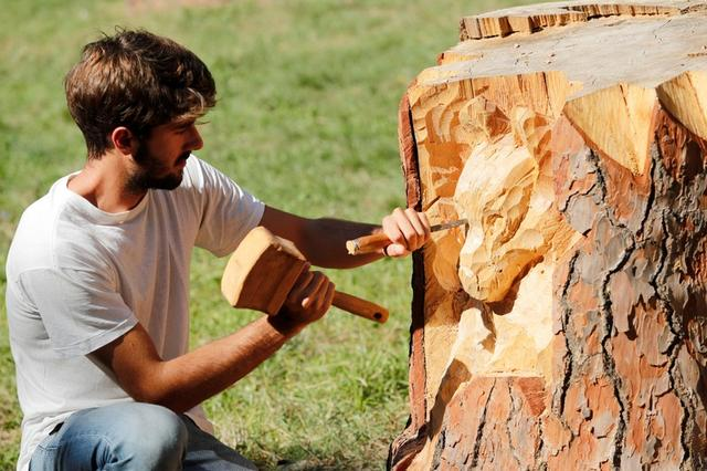 Sculptor Andrea Gandini carves a sculpture of a wolf's face from a dead tree stump in the Villa Pamphili park, Rome, Italy, October 18, 2019. Picture taken October 18, 2019 REUTERS/Remo Casilli
