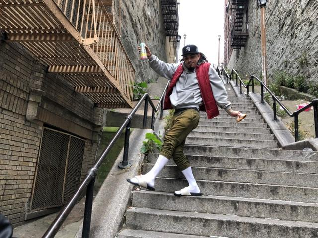 "FILE PHOTO: Jay Garcia, a radio host from Queens, dances down the ""Joker Steps"" in the Bronx borough of New York, U.S., October 16, 2019.REUTERS/Isabella Jibilian"