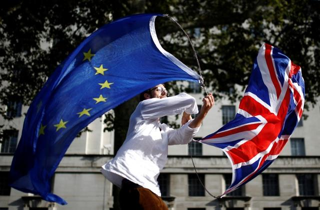 A EU supporter waves flags while other demonstrators march as parliament sits on a Saturday for the first time since the 1982 Falklands War, to discuss Brexit in London, Britain, October 19, 2019. REUTERS/Henry Nicholls