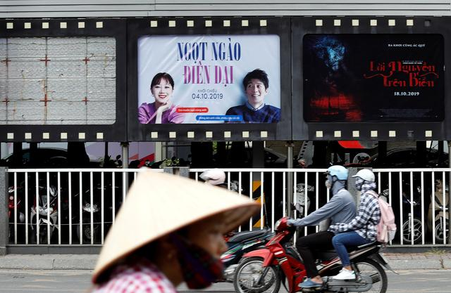 "FILE PHOTO: Bikers go past an empty space where a promotional poster for the DreamWorks film ""Abominable"" stood before being taken down at a cinema in Hanoi, Vietnam October 14, 2019. REUTERS/Kham"
