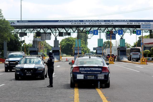 "Federal policemen keep watch at the Costa Rica toll as part of an operation to increase security after cartel gunmen clashed with federal forces, resulting in the release of Ovidio Guzman from detention, the son of drug kingpin Joaquin ""El Chapo"" Guzman, on the outskirts of Culiacan, in Sinaloa state, Mexico October 19, 2019. REUTERS/Stringer"