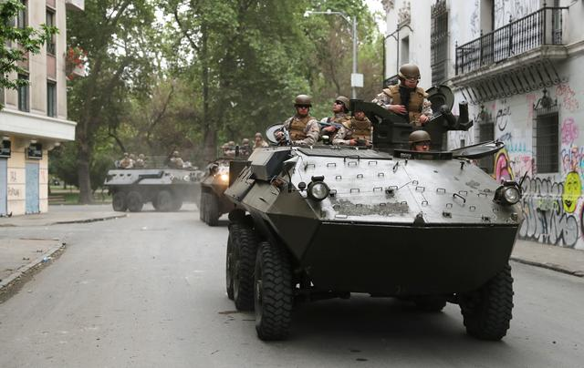 Soldiers ride an armoured transporter as they patrol a street after a previous day's protest against the increase in subway ticket prices in Santiago, Chile, October 20, 2019. REUTERS/Ivan Alvarado