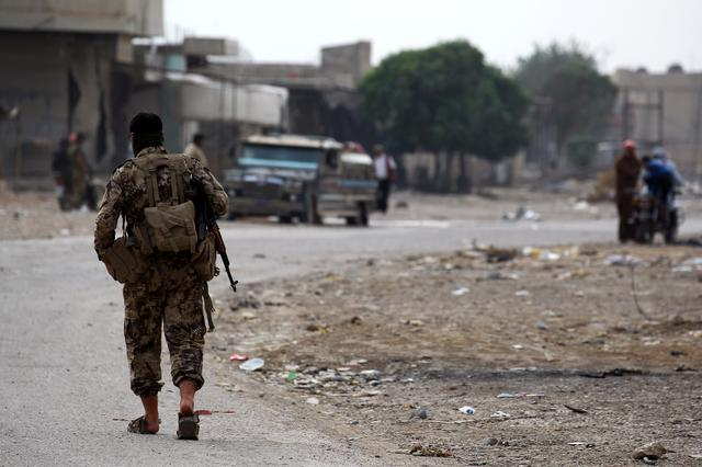 A Turkey-backed Syrian rebel fighter walks near Ras al Ain Town, Syria October 19, 2019. REUTERS/Aboud Hamam