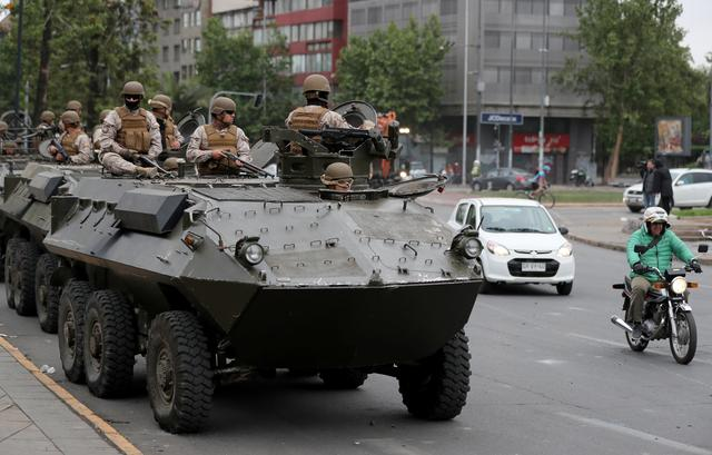 Soldiers ride an armoured transporter as they patrol the city after a previous day's protest against the increase in subway ticket prices in Santiago, Chile, October 20, 2019. REUTERS/Ivan Alvarado