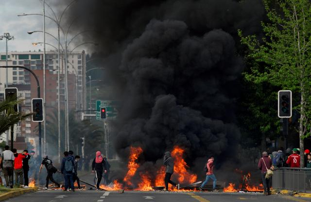 Demonstrators stand next to a burning barricade as increase in public transport prompted Chile's President Sebastian Pinera to declare a state of emergency, in Concepcion, Chile October 20, 2019.  REUTERS/Jose Luis Saavedra