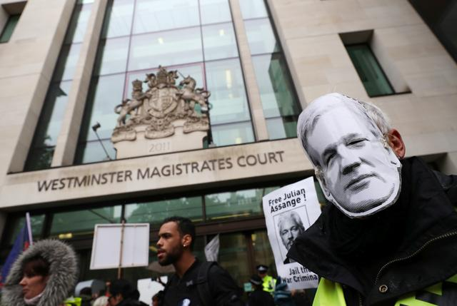 Demonstrators hold banners during a protest outside of Westminster Magistrates Court, where a case management hearing in the U.S. extradition case of WikiLeaks founder Julian Assange is held, in London, Britain, October 21, 2019. REUTERS/Hannah McKay